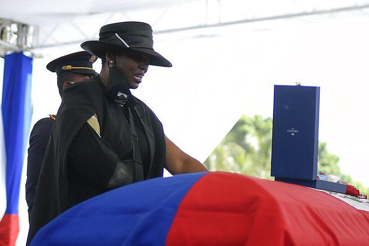 Mantan ibu negara Haiti, Martine Moise, berdiri di atas peti mati suaminya yang terbunuh, mantan Presiden Jovenel Moise, selama pemakamannya di rumah keluarganya di Cap-Haitien, Haiti, Jumat, 23 Juli 2021.