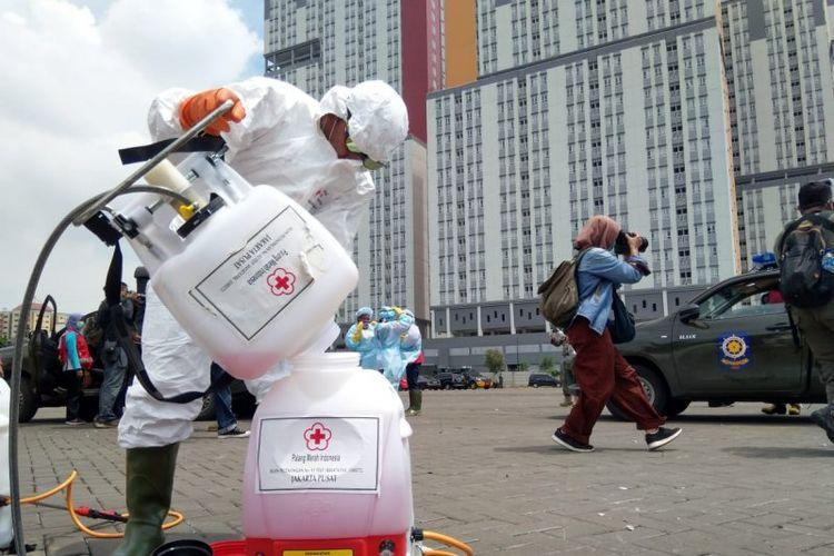 Petugas dari PMI Jakarta Pusat bersiap menyemprotkan disinfektan di dua menara Wisma Atlet Kemayoran, Jakarta, Sabtu (21/3/2020).