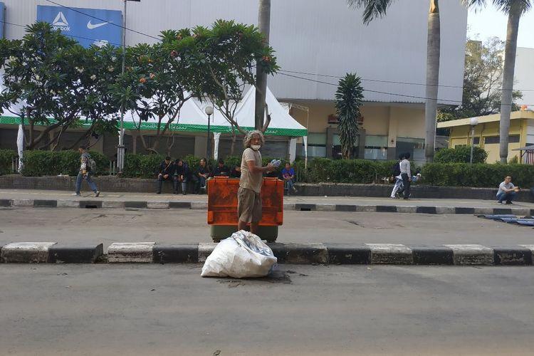 Seorang pemulung mengobok-obok bak sampah di Jalam KH Wahid Hasyim Jakarta Pusat seusai kericuhan yang berlangsung sampai Kamis (23/5/2019) subuh.