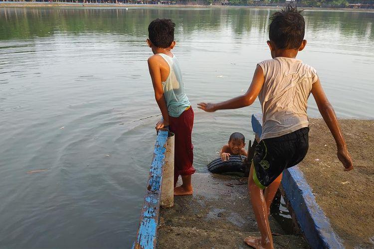 Anak-anak kecil bermain air di Setu Babakan, Jakarta Selatan, Jumat (17/5/2019).