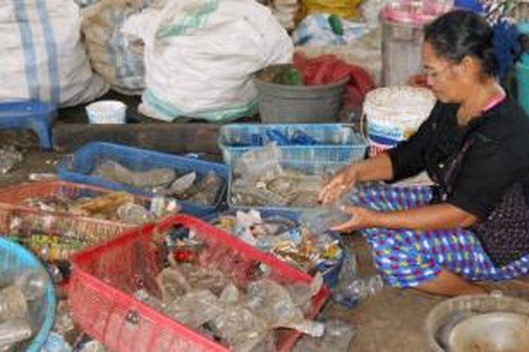 Buruh Di Tempat Daur Ulang Sampah Plastik, Hanasiah (46), sedang memilah-milah sampah plastik. Walau kerjanya sebagai buruh sampah, ia masih bisa membantu perekonomian keluarganya