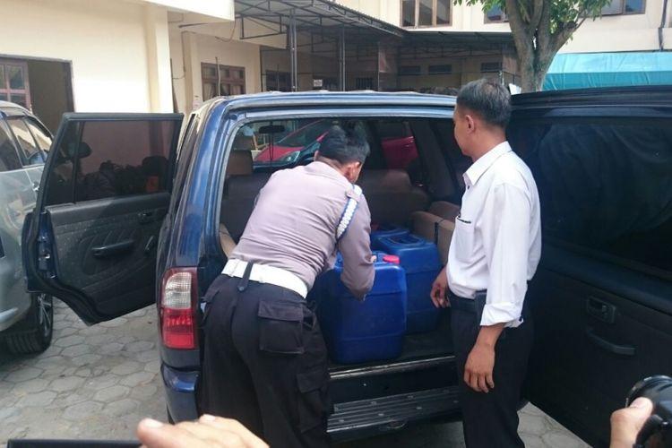 Anggota Reskrim Polres Magetan menunjukkan mobil dinas DPRD Magetan yang diamankan lantaran kedapatan mengangkut arak jowo (arjo) di Mapolres Magetan, Senin ( 7 / 8 / 2017) sore.