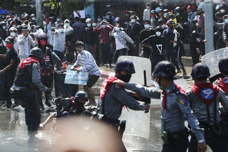 Pengunjuk rasa berlarian setelah polisi memberikan tembakan peringatan dan menggunakan meriam air untuk membubarkan demonstrasi di Mandalay, Myanmar, pada 9 Februari. Polisi bergerak setelah massa berdemonstrasi menentang kudeta militer Myanmar.