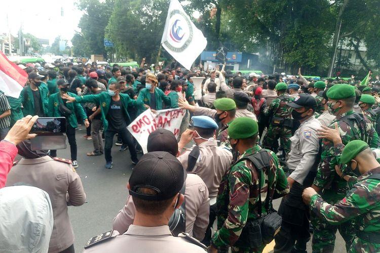 Massa mahasiswa di Bogor terlibat aksi saling dorong dengan aparat kepolisian saat menggelar unjuk rasa menolak pengesahan Undang-undang Cipta Kerja di depan Istana Bogor, Kamis (8/10/2020).