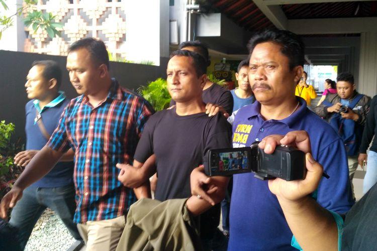 Jose William Salasar (tengah, berkaos hitam) saat digiring petugas setiba di Bandara Ngurah Rai, Bali, Kamis (25/5/2017), sesudah kabur selama 8 hari dan tertangkap lagi di Pekanbaru, Riau. Dia adalah terdakwa kasus pembobolan ATM yang kabur dari sel tahanan Pengadilan Negeri Denpasar pada Selasa (16/5/2017).