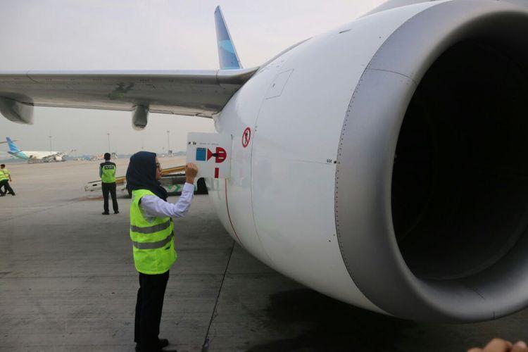 Staf teknisi perempuan Garuda Indonesia memeriksa bagian pesawat.