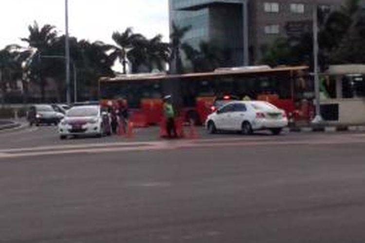 Polisi lalu lintas memberi peringatan pada pengendara motor melalui pengeras suara dalm mobil patroli di Bundaran HI, Rabu (17/12/2014).