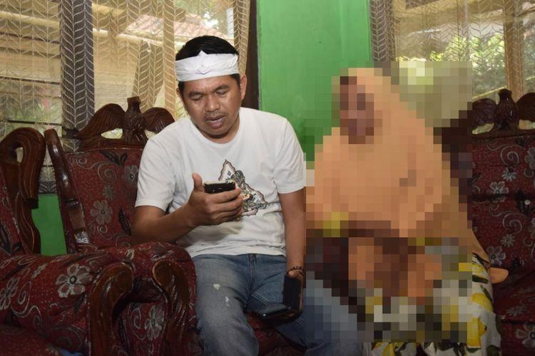 Dedi Mulyadi membaca pesan WhatsApp dari salah satu korban perdagangan orang, saat mengunjungi salah satu rumah orangtua korban di Purwakarta, Sabtu (27/7/2018).