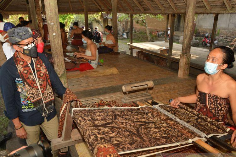 Menteri Pariwisata dan Ekonomi Kreatif (Menparekraf) Sandiaga Salahuddin Uno berbincang dengan perajin kain tenun di Desa Tenganan, Kabupaten Karangasem, Bali, Jumat (24/9/2021).
