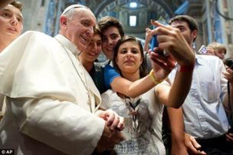 Paus Fransiskus mengambil foto diri sendiri menggunakan telepon genggam atau selfie bersama para remaja di Basilika Santo Petrus, Vatikan.
