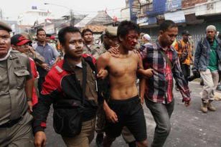 Seorang warga Kampung Pulo, Jakarta Timur, tertangkap saat terlibat kerusuhan dengan Satpol PP dan polisi di Jalan Jatinegara Barat, Kamis (20/8/2015). Kerusuhan terjadi karena warga menolak digusur dan dipindahkan untuk normalisasi Kali Ciliwung.