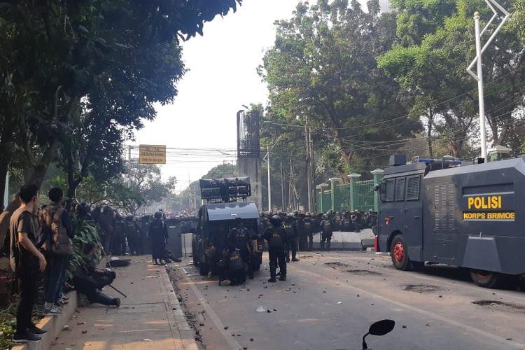 Polisi bersiaga di pintu belakang Kompleks DPR RI, Jalan Gelora, Jakarta Pusat, Rabu (25/9/2019). Mereka berupaya menghalau massa pelajar yang berupaya masuk ke Gedung DPR.