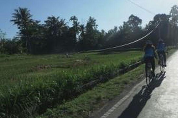 Para pesepeda melewati jalur aspal dengan pemandangan sawah di kiri jalan menuju titik pemberhentian pertama di Desa Pemepek, Kecamatan Pringgarata, Kabupaten Lombok Tengah, Kamis (9/4/2015). Etape 1 Tambora Bike akan berakhir di Desa Utan, Kecamatan Utan, Kabupaten Sumbawa, Nusa Tenggara Barat.