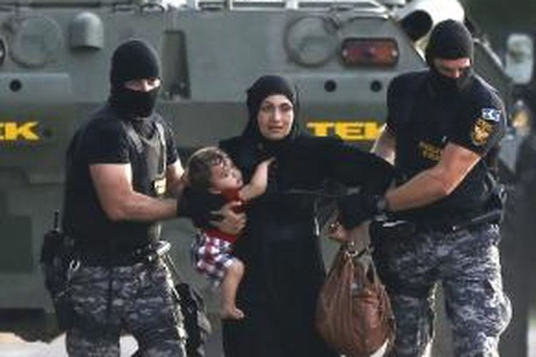 polisi hungaria menarik migran yang sedang menggendong anaknya