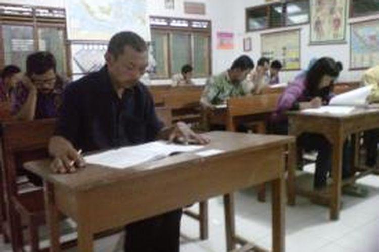Peserta UN Kejar Paket C sedang mengerjakan soal ujian di SD Negeri Borobudur 2, Kabupaten Magelang, Senin (13/4/2015).