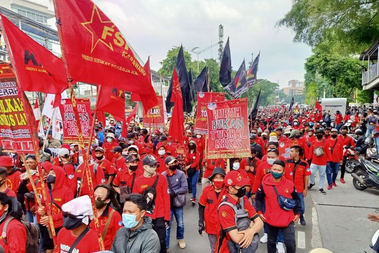 Massa buruh berjalan kaki di Jalan Salemba Raya, Jakarta Pusat, menuju kawasan Monas dalam rangkaian aksi penolakan Undang-Undang Cipta Kerja, Selasa (20/10/2020).