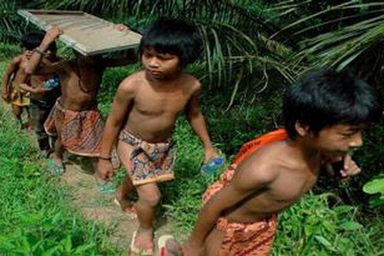 Anak-anak rimba menempuh perjalanan menuju lokasi belajar bersama dalam Taman Nasional Bukit Duabelas, Sarolangun, Jambi, Jumat (26/4/2013). Pendidikan khusus melalui pendekatan budaya lokal yang dilaksanakan relawan dari Komunitas Konservasi Indonesia (KKI) Warsi telah menjadikan lebih dari 400 anak rimba melek huruf.
