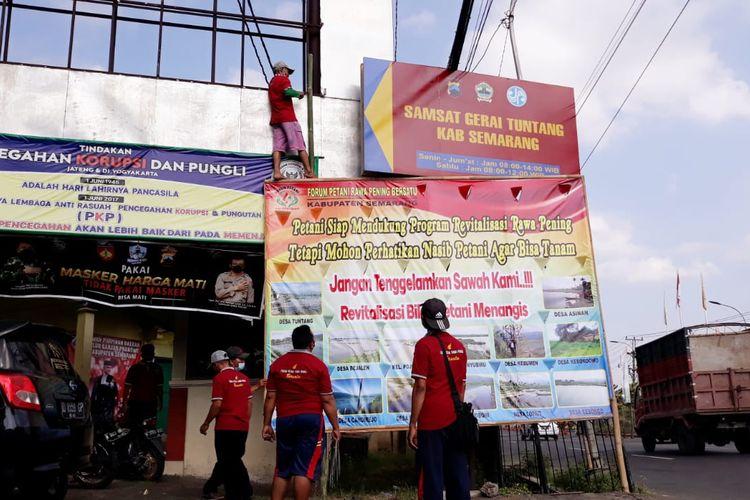 Anggota FPRPB memasang spanduk protes akibat tidak bisa menanam padi.