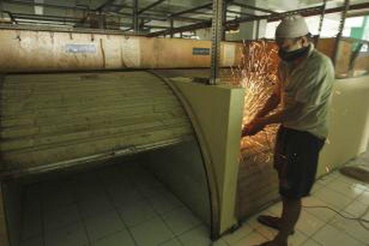 Pekerja memperbaiki sejumlah rolling door kios yang rusak di Pasar Tanah Abang Blok G, Jakarta, Sabtu (10/8/2013). Perbaikan Blok G terus dilakukan. Pemerintah Provinsi DKI Jakarta berencana mulai menertibkan PKL di Tanah Abang dan memindahkannya ke Blok G setelah libur Lebaran.