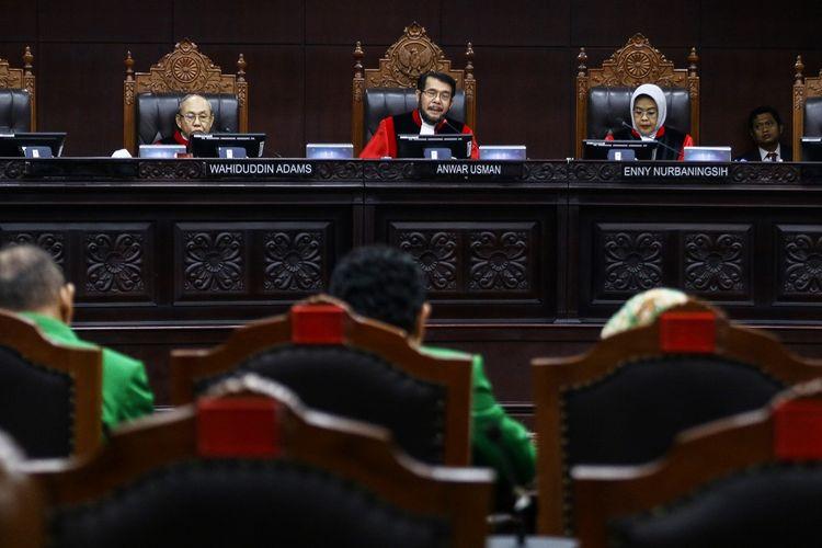 Ketua Majelis Hakim Mahkamah Konstitusi (MK) Anwar Usman (tengah) didampingi Majelis Hakim MK Wahiduddin Adams (kiri) dan Enny Nurbaningsih (kanan) memimpin sidang pendahuluan uji formil Undang-Undang KPK di Gedung MK, Jakarta, Senin (14/10/2019). Sidang tersebut menguji tentang perubahan kedua atas Undang-Undang Nomor 30 Tahun 2002 tentang Komisi Pemberantasan Tindak Pidana Korupsi terhadap Undang-Undang Dasar Negara Republik Indonesia 1945 terkait dewan pengawas KPK. ANTARA FOTO/Rivan Awal Lingga/foc.
