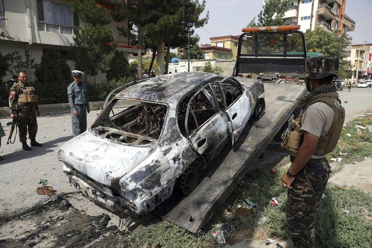 Personel keamanan menginspeksi kendaraan yang terbakar saat roket menghantamnya di Kabul, Afghanistan, pada 20 Juli. Setidaknya tiga roket jatuh dekat istana kepresidenan di tengah pelaksanaan Shalat Idul Adha.