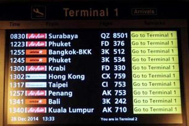 Informasi penerbangan termasuk AirAsia QZ8501 (atas), di terminal 1 Bandara Internasional Changi di Singapura, 28 Desember 2014. Pesawat AirAsia QZ8501 yang mengangkut 155 penumpang serta 7 awak, hilang kontak pada Minggu pagi, saat penerbangan dari Surabaya menuju Singapura.