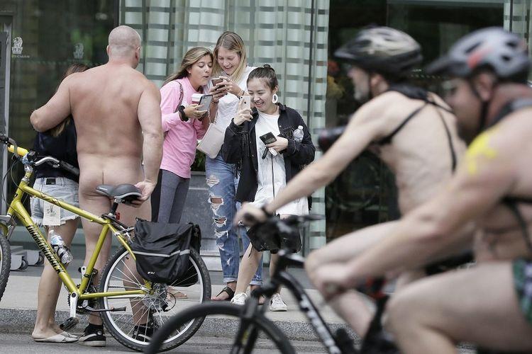 Seorang pengendara sepeda tanpa busana berpose untuk berfoto saat peserta lain melewatinya selama Philly Naked Bike Ride pada 8 September 2018 di Philadelphia. Tahun 2020, Philly Naked Bike Ride dibatalkan karena pandemi virus corona.