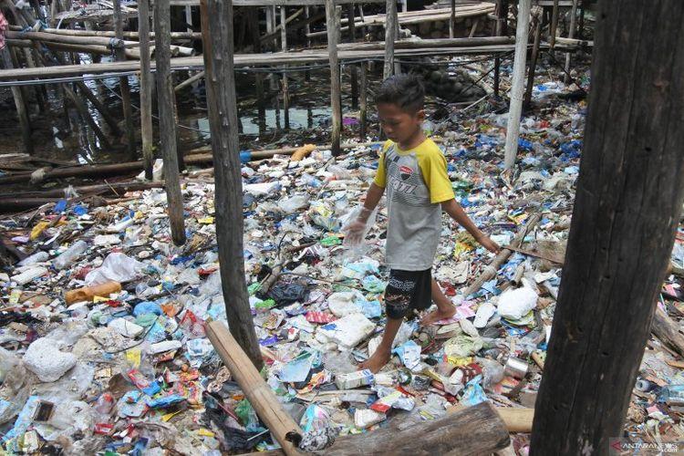 Seorang anak berjalan di atas tumpukan sampah di perkampungan nelayan Wuring, Kelurahan Wolomarag, Kecamatan Alok Barat, Kabupaten Sikka, Kamis (12/3). (Foto : Antara/Kornelis Kaha).