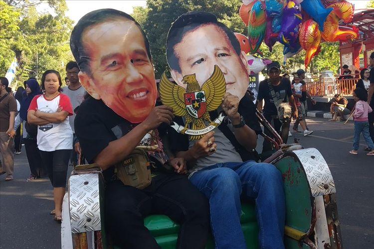 Warga memakai topeng Jokowi dan Prabowo naik becak di car free day (CFD) Jalan Slamet Riyadi Solo, Jawa Tengah, Minggu (14/7/2019).