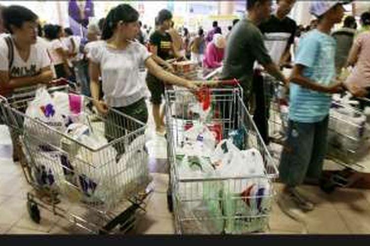 KOMPAS/WISNU WIDIANTORO Pembeli bersiap membawa belanjaan mereka yang dibungkus kantong plastik di sebuah pasar swalayan di Jakarta, beberapa waktu lalu. Pemerintah berencana menerapkan pembatasan kantong plastik untuk mengurangi sampah plastik.
