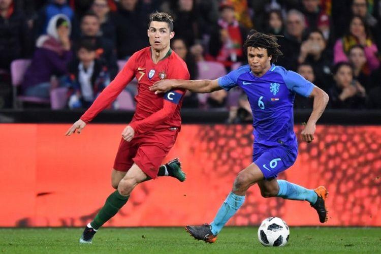 Cristiano Ronaldo dan Nathan Ake berebut bola pada pertandingan uji coba antara Portugal dan Belanda di Geneva, Senin (26/3/2018).