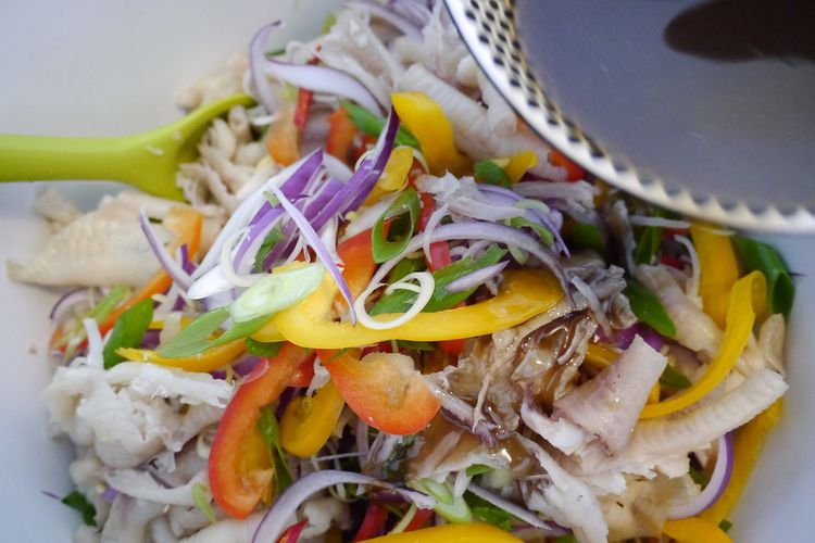 Salad ceker ayam  khas Laos Yum Tien Gai dituangi kecap ikan.
