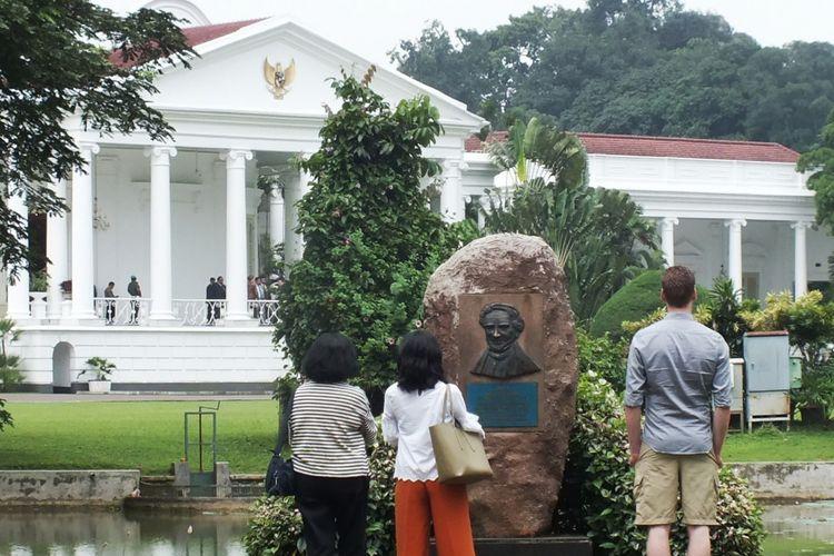 Sejumlah pengunjung Kebun Raya Bogor sedang melihat-lihat pemandangan berlatar belakang Istana Kepresidenan Bogor, Rabu (13/1/2019).