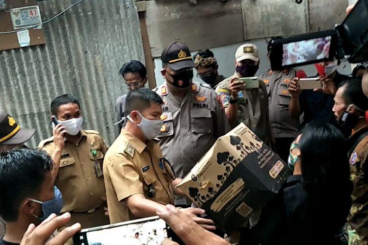 Petugas gabungan yang terdiri dari Polisi, Satpol PP hingga petugas Kelurahan Pluit ikut turun tangan membagikan langsung bantuan sosial kepada warga di RT 02 RW 022, Muara Angke, Pluit, Penjaringan, Jakarta Utara, Selasa (24/11/2020) sore.