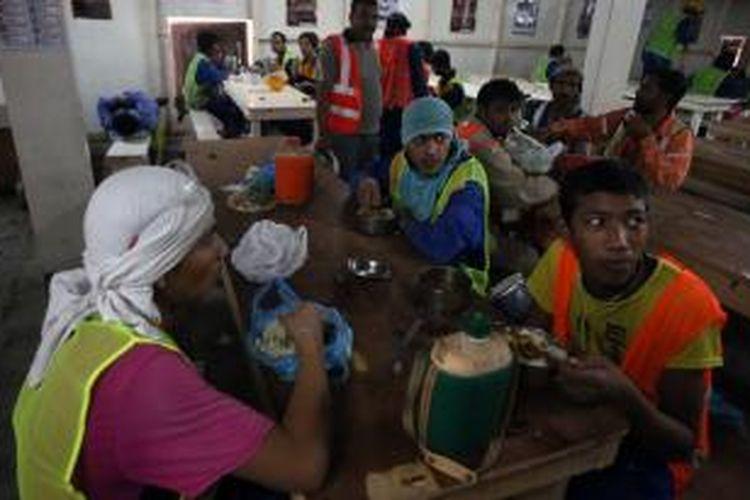Para pekerja migran asal Asia Selatan yang bekerja dalam proyek pembangunan stadion Piala Dunia 2022 tengah beristirahat makan siang. Beberapa media menuding Qatar memperlakukan para pekerja asing ini dengan sangat buruk.