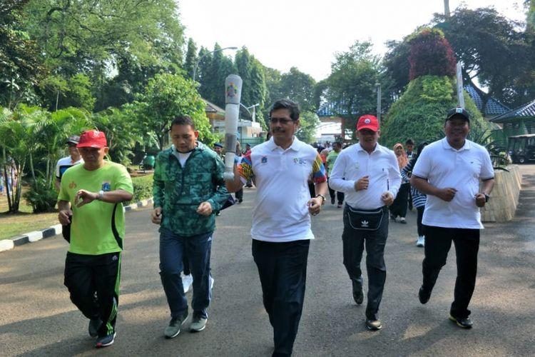 Wali Kota Jakarta Selatan Marullah Matali berlatih lari membawa replika obor Asian Games prosesi Torch Relay Asian Games 2018 di kawasan Taman Margasatwa Ragunan, Jumat (20/7/2018).