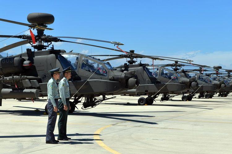 Dua tentara Taiwan berdiri di depan helikopter serbu Apache AH-64E buatan AS saat upacara komisioning di pangkalan militer di Taoyuan, Selasa (17/7/2018).