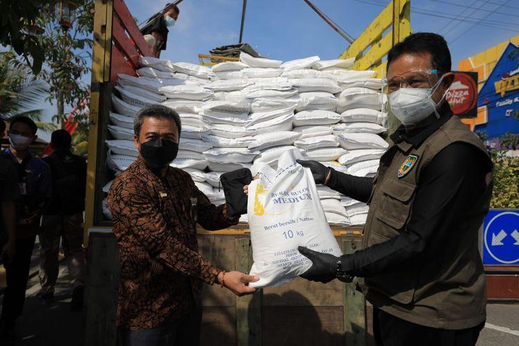 Wali Kota Madiun Maidi menunjukkan beras medium dari Kemensos yang diberikan kepada warga terdampak Covid-19 di depan Balai Kota Madiun, Jumat (6/8/2021).