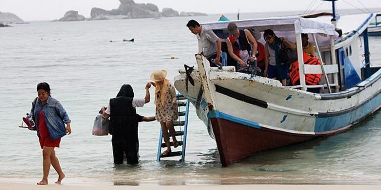 Wisatawan turun dari perahu motor yang mengantar mereka mengunjungi beberapa pulau di perairan dekat Pantai Tanjung Kelayang, Kabupaten Belitung, Kepulauan Bangka Belitung, Kamis (18/12/2014). Hujan sejak pagi tidak menyurutkan sejumlah wisatawan mengunjungi pulau-pulau menawan di kawasan itu, seperti Pulau Lengkuas dan Kepayang.