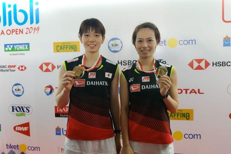 Pasangan ganda putri Jepang, Yuki Fukushima/Sayaka Hirota, memamerkan medali emas Indonesia Open 2019 yang sukses mereka raih pada Minggu (21/7/2019).