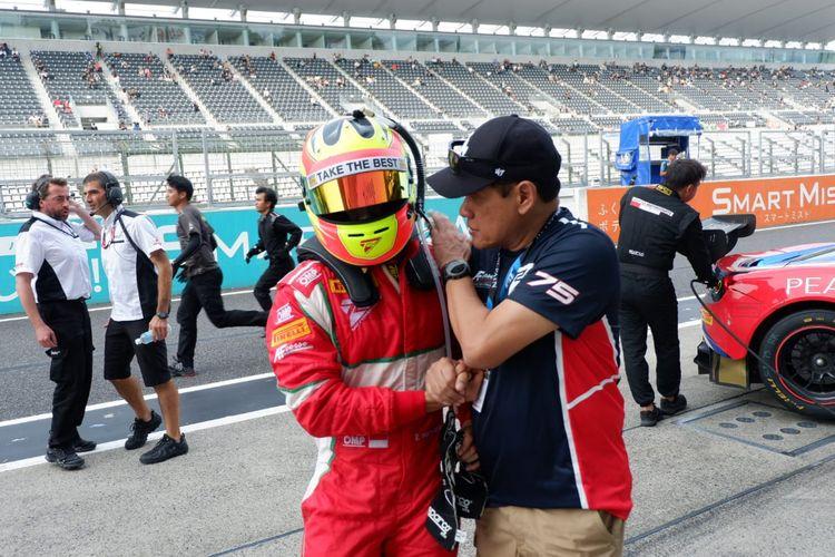 Pebalap Rio Haryanto (kiri) berbincang dengan Team Principal T2 Motorsports, Irmawan Poedjoadi, usai race pertama seri ketiga Blancpain GT World Challenge Asia 2019 di Sirkuit Suzuka, Jepang, Sabtu (22/6/2019).