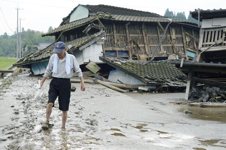 Seorang pria berjalan di jalanan yang terendam lumpur usai banjir besar di Desa Kuma, Prefektur Kumamoto, Jepang, pada Minggu (5/7/2020). Hujan deras di Kumamoto memicu banjir besar dan tanah longsor, yang membuat puluhan orang terjebak di rumah dan bangunan-bangunan lainnya.