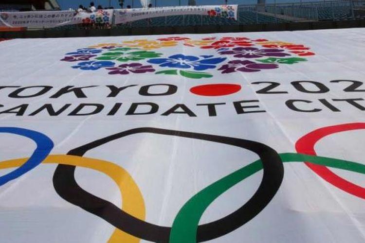 Warga berdiri melihat api yang menyala di kaldron Olimpiade, yang digunakan dalam Olimpiade Tokyo 1964, di dekat banner bertuliskan logo resmi Tokyo untuk Olimpiade 2020 di Stadion Nasional, 1 September 2013.