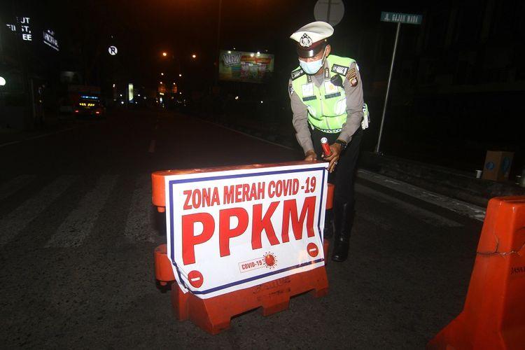 Seorang petugas kepolisian melaksanakan operasi penyekatan PPKM skala Mikro di kawasan pusat perdagangan di Jalan Gajahmada, Pontianak, Kalimantan Barat, Selasa (6/7/2021) malam. Pemerintah daerah setempat bersama kepolisian menutup sejumlah kawasan serta membatasi waktu operasional kegiatan usaha yaitu pukul 14.00 - 17.00 WIB dan 19.00 - 23.00 WIB guna mencegah kerumunan masyarakat karena Pontianak masuk dalam zona merah penyebaran COVID-19. ANTARA FOTO/Jessica Helena Wuysang/wsj.