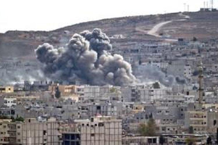 Asap terlihat mengepul di atas kota Kobani setelah serangan udara AS dilihat dari kota Suruc, Turki