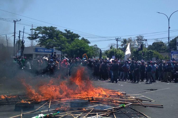 Massa mahasiswa dari berbagai kampus di Makassar saat membakar karangan bunga berisi ucapan selamat anggota DPRD Sulsel yang baru, Selasa (24/9/2019).