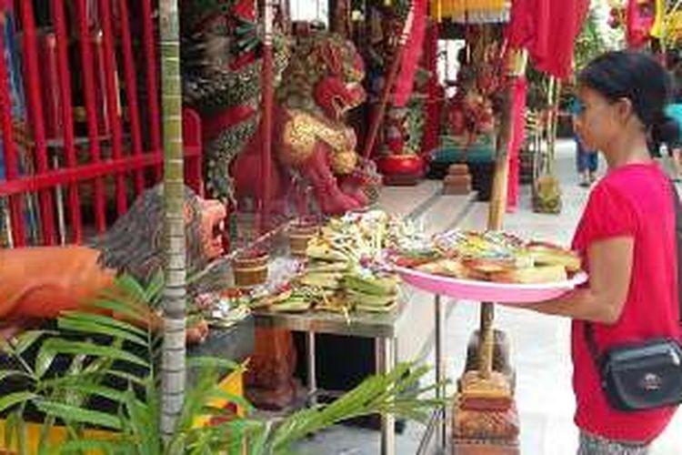 Umat Buddha menghaturkan Canang atau sesaji bunga di Vihara Dharmayana, Jalan Blambangan, Kuta, Badung, Bali, Minggu (7/2/2016).