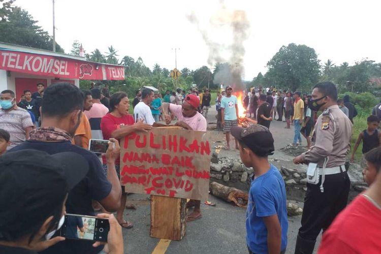 Warga Desa Watludan Kecamatan Waipia, Kabupaten Maluku Tengah memblokade Jalan Trans Seram, Kamis petang (8/7/2021). Pemblokiran jalan dilakukan warga setelah mereka mengambil jenazah pasien positif di RSUD Masohi
