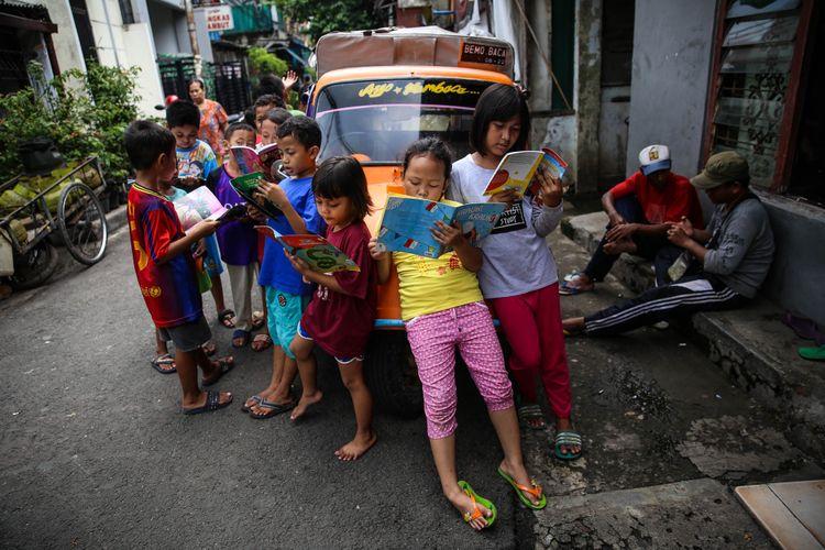 Anak-anak membaca buku di bemo perpustakaan di Jalan Karet Pasar Baru Barat II, Tanah Abang, Jalarta Pusat, Jumat (7/12/2018). Pak Sutino (58) adalah sopir bemo yang merintis bemo tuanya menjadi perpustakaan keliling bagi anak-anak sejak tahun 2013.  Pak Sutino (58) adalah sopir bemo yang merintis bemo tuanya menjadi perpustakaan keliling bagi anak-anak sejak tahun 2013.