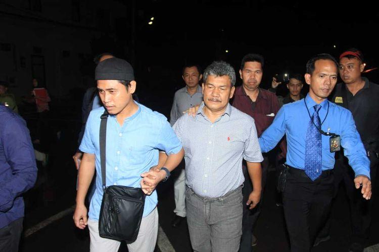Wakil Bupati Ogan Komering Ulu (OKU) Johan Anwar saat dibawa penyidik Polda Sumatera Selatan menuju ruang tahanan. Johan ditahan setelah sebelumnya menjalani pemeriksaan terkait mark up lahan kuburan selama 12 jam, Selasa (14/1/2020).